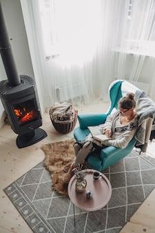 Jonge vrouw schrijft in notitieboekje zittend in fauteuil bij open haard
