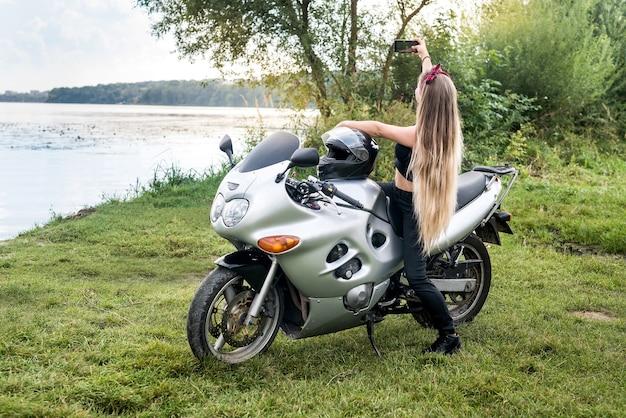 Jonge vrouw selfie maken op motor buitenshuis