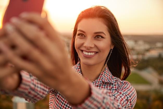 Jonge vrouw selfie te nemen tijdens zonsondergang