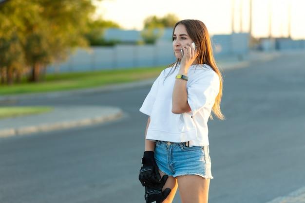 Jonge vrouw skateboarder in sporthandschoenen die op een mobiele telefoon met een peinzend gezicht spreken