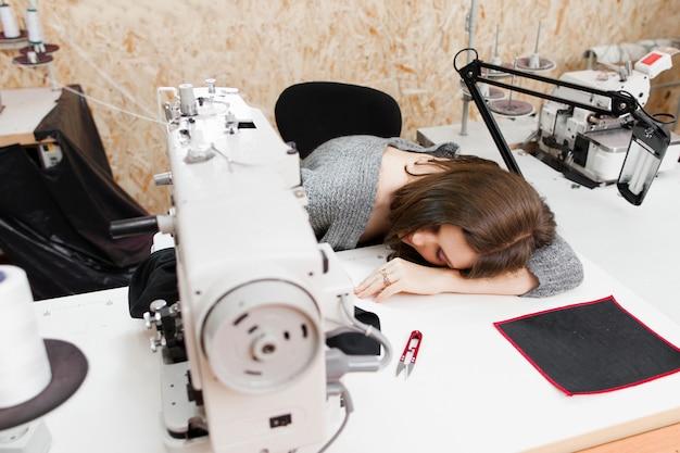 Jonge vrouw slaapt door haar naaimachine.