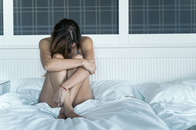 Jonge vrouw slachtoffer van gendergeweld in haar bed. concept van misbruik en geweld tegen vrouwen.