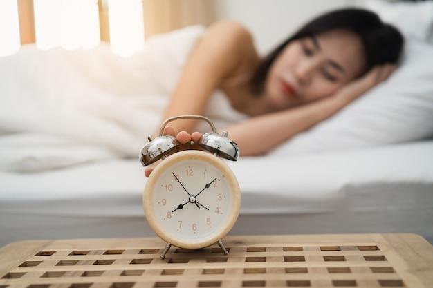 Jonge vrouw slapen en wekker in de slaapkamer thuis