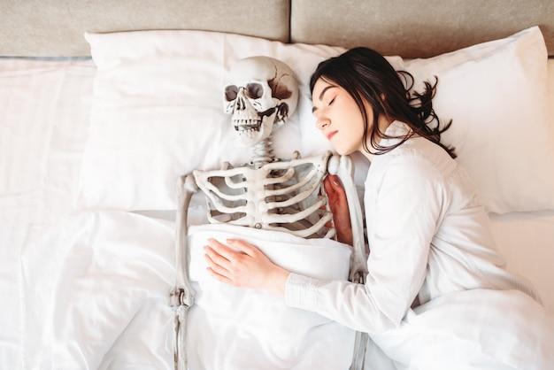 Jonge vrouw slapen in slechte met grappig menselijk skelet samen, bovenaanzicht.