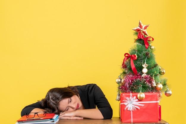 Jonge vrouw slapen zittend aan een tafel in de buurt van versierde kerstboom op kantoor op geel