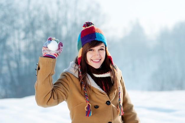 Jonge vrouw sneeuwbal gooien