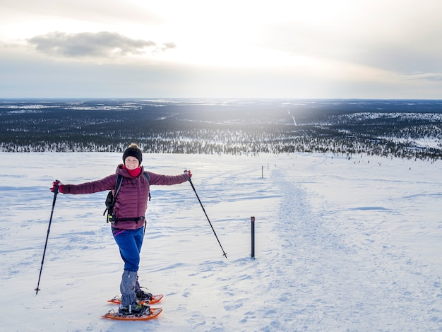 Jonge vrouw sneeuwschoenwandelen en genieten van prachtig winterweer