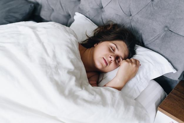Jonge vrouw snel in slaap slapen in haar bed op wit beddengoed