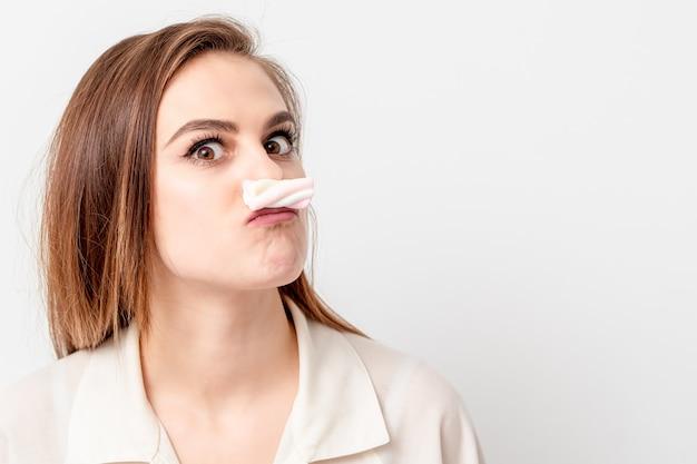 Jonge vrouw snor met zoete snoep marshmallow maken op witte achtergrond. ontharen en epileren concept.
