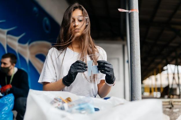 Jonge vrouw sorteren vuilnis