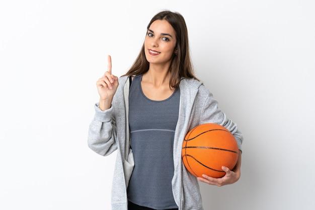 Jonge vrouw speelbasketbal geïsoleerd op een witte achtergrond tonen en opheffen van een vinger in teken van het beste