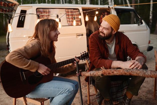 Jonge vrouw speelt gitaar en zingt samen met haar vriendje terwijl ze tijd doorbrengen met picknicken