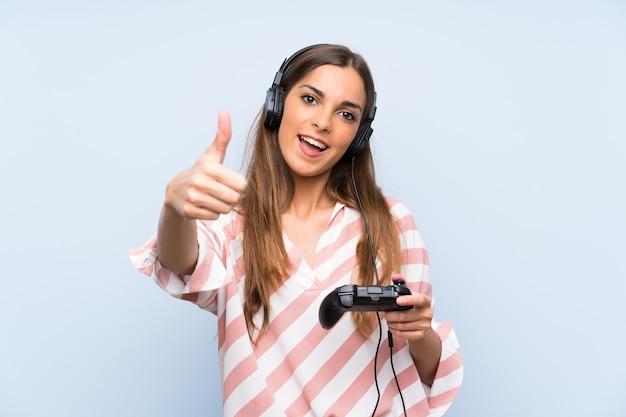 Jonge vrouw speelt met een videogamecontrolemechanisme met omhoog duimen omdat er iets goeds is gebeurd