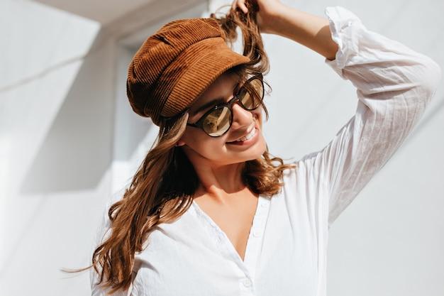 Jonge vrouw speelt met haar haren en glimlacht. meisje gekleed in witte blouse, bruine hoed en zonnebril poseren tegen wit gebouw.