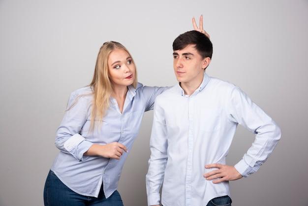 Jonge vrouw speelt met haar vriendje op grijze muur.