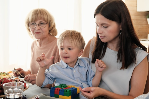 Jonge vrouw speelt met haar zoontje terwijl ze aan de eettafel zitten die ze haar ouders bezoekt