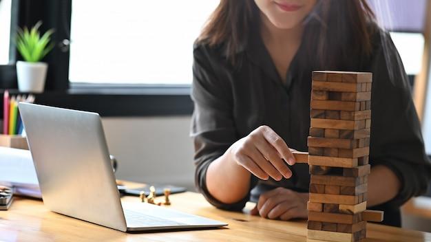 Jonge vrouw speelt met houten blokken in het kantoor