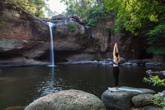 Jonge vrouw speelt yoga voor de waterval Premium Foto