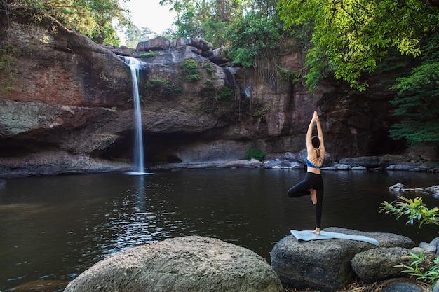 Jonge vrouw speelt yoga voor de waterval
