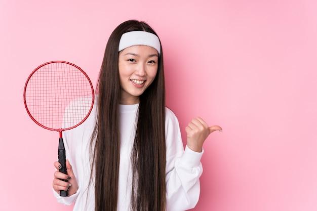 Jonge vrouw spelen badminton geïsoleerde punten met duim vinger weg, lachen en zorgeloos