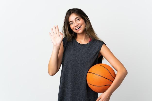 Jonge vrouw spelen basketbal geïsoleerd groeten met hand met gelukkige uitdrukking
