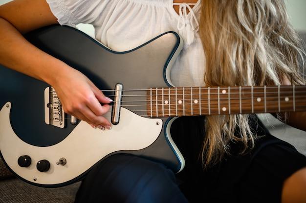 Jonge vrouw spelen een gitaar zittend op haar bank thuis