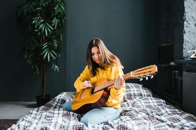 Jonge vrouw spelen op akoestische gitaar thuis, zittend op het bed