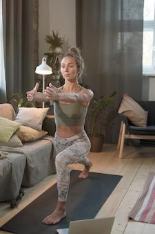 Jonge vrouw sport beoefening in de woonkamer tijdens lockdown