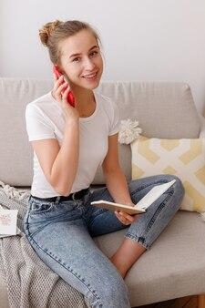 Jonge vrouw spreekt aan de telefoon in de woonkamer