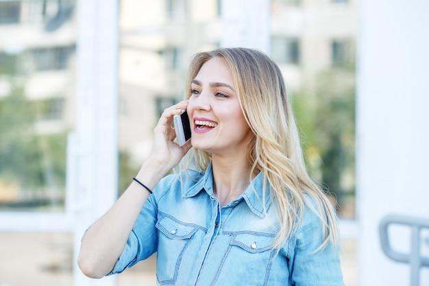 Jonge vrouw spreekt op de telefoon in de straat