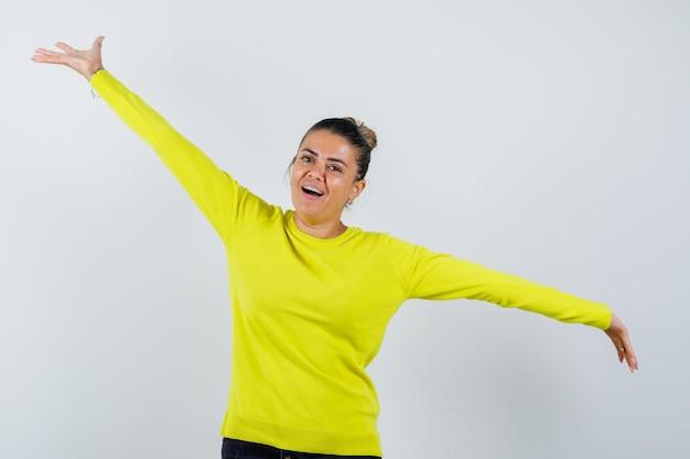 Jonge vrouw spreidt armen opzij in trui, spijkerrok en ziet er energiek uit