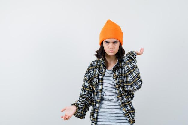 Jonge vrouw spreidt handpalmen in oranje hoed en geruit hemd en ziet er somber uit
