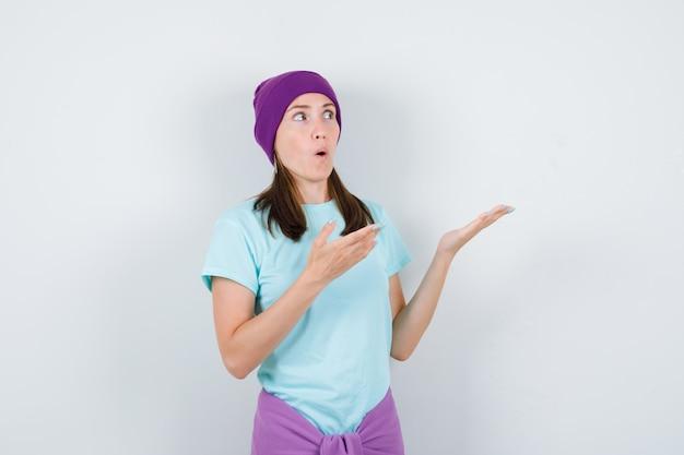 Jonge vrouw spreidt handpalmen opzij, houdt mond open in blauw t-shirt, paarse muts en kijkt verrast. vooraanzicht.