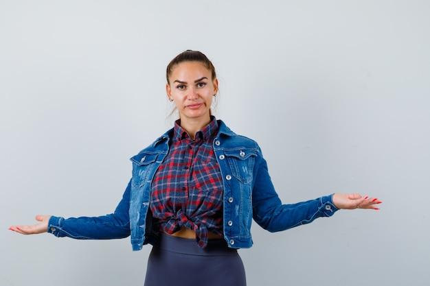 Jonge vrouw spreidt handpalmen opzij in geruit hemd, jas, broek en kijkt aarzelend, vooraanzicht.