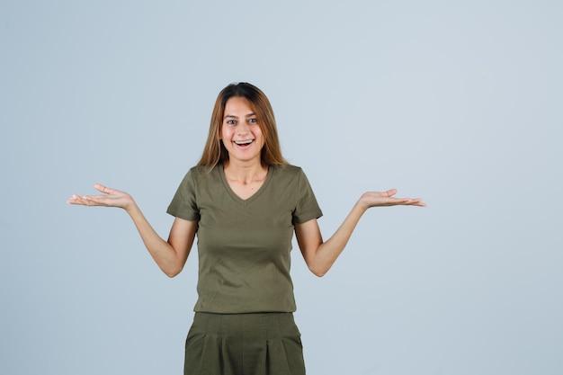 Jonge vrouw spreidt handpalmen opzij in t-shirt, broek en ziet er gelukkig uit, vooraanzicht.