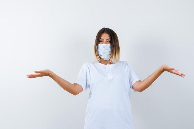 Jonge vrouw spreidt handpalmen opzij in t-shirt, masker en kijkt zelfverzekerd, vooraanzicht.