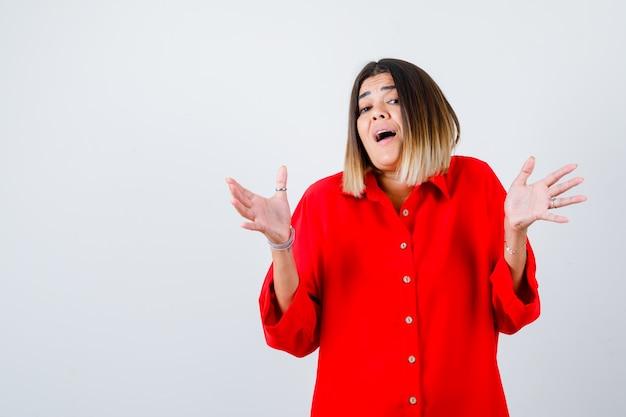 Jonge vrouw spreidt handpalmen uit in rood oversized shirt en kijkt verbaasd, vooraanzicht.