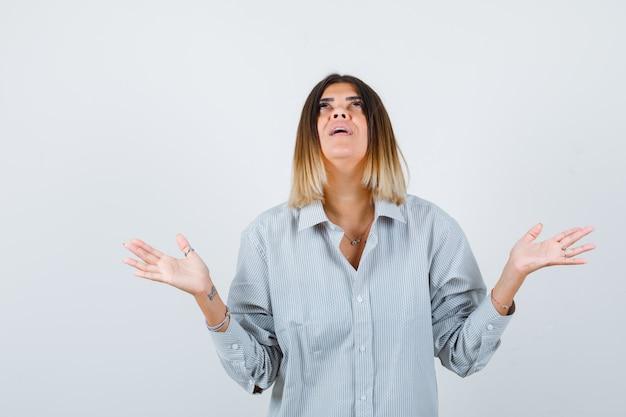Jonge vrouw spreidt handpalmen uit om te bidden in een te groot shirt en ziet er hoopvol uit, vooraanzicht.
