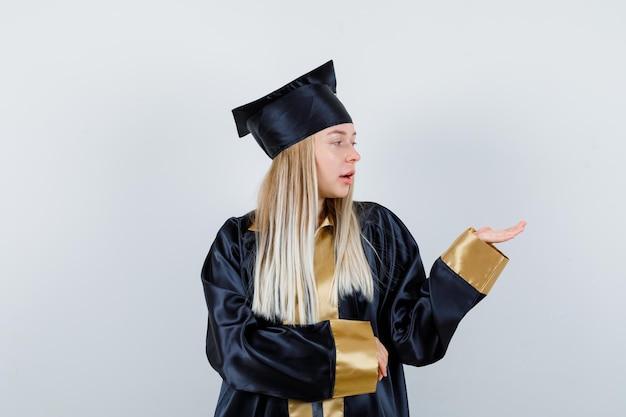 Jonge vrouw spreidt palm opzij in afgestudeerd uniform en kijkt gefocust.