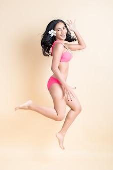 Jonge vrouw springen in badkleding