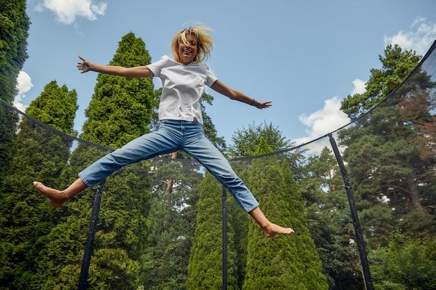 Jonge vrouw springen op trampoline buiten