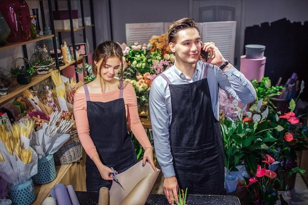Jonge vrouw staan aan tafel en gesneden stuk papier rollen. man staat achter haar en praat over de telefoon. hij glimlacht. ze staan in een kamer vol bloemen en planten.