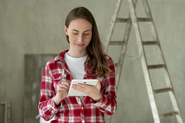 Jonge vrouw staan in nieuw appartement met behulp van tablet kiezen nieuw ontwerp van huis huis reparatie
