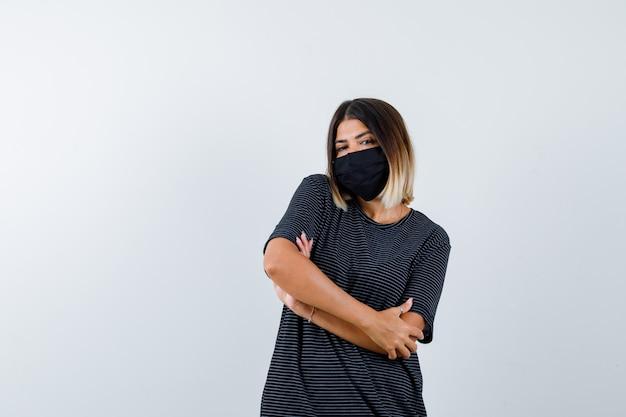 Jonge vrouw staande armen gekruist in zwarte jurk, zwart masker en op zoek verward, vooraanzicht.