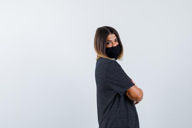 Jonge vrouw staande armen gekruist, kijkend over de schouder in zwarte jurk, zwart masker en op zoek gelukkig, vooraanzicht.