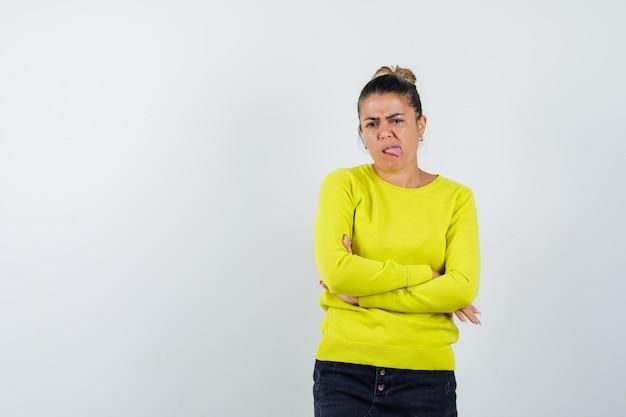 Jonge vrouw staande armen gekruist, tong uitgestoken in gele trui en zwarte broek en gehaast kijken