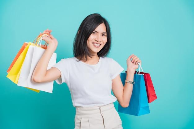 Jonge vrouw staande houden boodschappentassen multi kleur