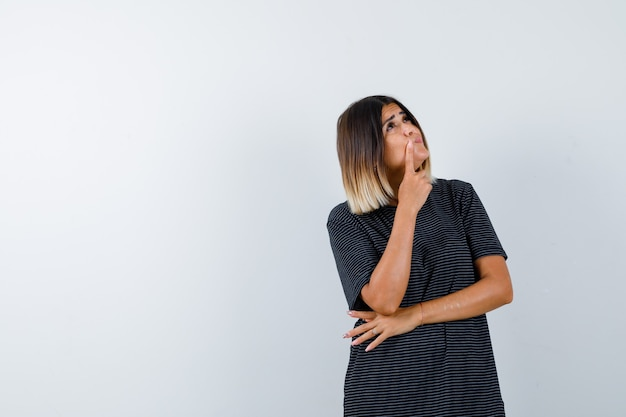 Jonge vrouw staande in denken pose in polokleding en op zoek attent, vooraanzicht.