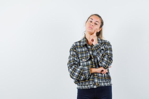 Jonge vrouw staande in denken pose in shirt, korte broek en schattig op zoek. vooraanzicht.