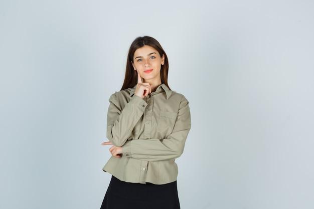 Jonge vrouw staande in denken pose in shirt, rok en op zoek zelfverzekerd